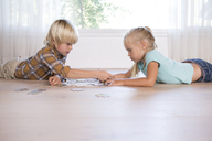 Brother and sister lying on the floor at home playing jigsaw puzzle - MFRF01119