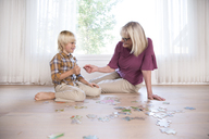Boy and grandmother playing jigsaw puzzle on the floor at home - MFRF01122