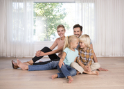 Relaxed family sitting on the floor at home - MFRF01125