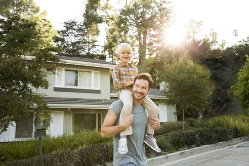 Happy boy on father's shoulders in front of their home - MFRF01128