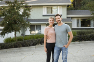 Portrait of smiling couple in front of their home - MFRF01131