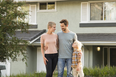 Smiling parents with boy standing in front of their home - MFRF01134