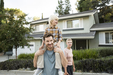 Portrait of smiling parents with son in front of their home - MFRF01137