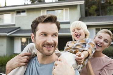 Happy parents with son in front of their home - MFRF01140