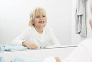 Smiling boy with teeth gap looking in bathroom mirror - MFRF01149