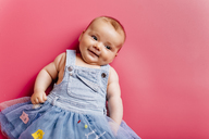 Portrait of smiling baby girl lying on pink background - JRFF01488