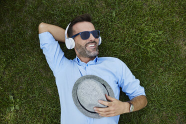 Portrait of laughing man relaxing on a meadow listening music with headphones, top view - BSZF00138