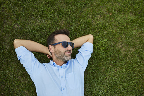 Man wearing sunglasses relaxing on a meadow, top view - BSZF00141