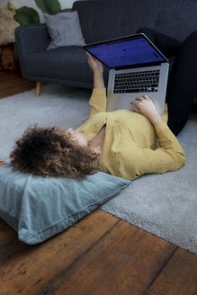 Young woman lying on the floor at home using laptop - HHLMF00061