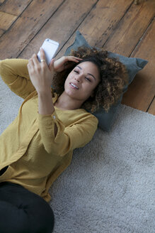 Smiling young woman lying on the floor at home with cell phone - HHLMF00064