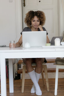 Smiling young woman sitting at table at home using laptop - HHLMF00067