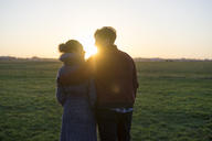 Young couple walking on a meadow at sunset - HHLMF00106