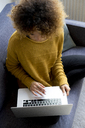 Young woman sitting on couch at home using laptop - HHLMF00112
