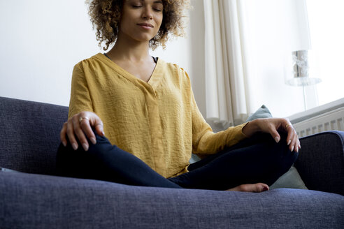 Young woman sitting on couch at home meditating - HHLMF00115
