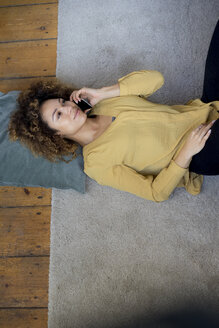 Young woman on cell phone lying on the floor at home - HHLMF00121