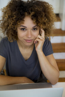 Portrait of smiling young woman with laptop - HHLMF00124
