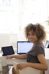 Portrait of smiling young woman at home with laptop and tablet - HHLMF00127