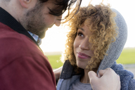 Portrait of smiling young couple close together outdoors - HHLMF00136