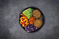 Lunch bowl of quinoa, red cabbage, bell pepper, avocado, quinoa fritters, ajvar and black sesame - LVF06574