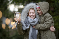 Happy teenage girl and her little sister with self-made gift outdoors - LBF01708