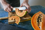 Hands of senior man cutting papaya - KIJF01824