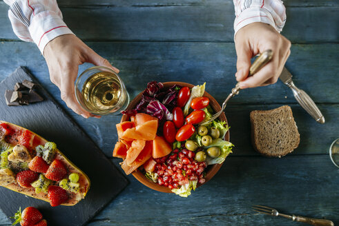 Close-up of woman's hands eating salad wit tomato, pomegranate, papaya and olives, papaya with fruits and with wine glass - KIJF01833