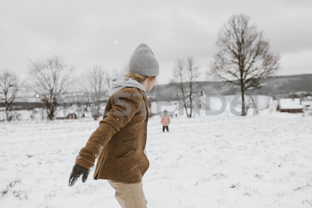 Boy and his little sister playing together in snow-covered landscape - KMKF00114