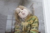 Portrait of little girl sticking out tongue while looking out of window - KMKF00117