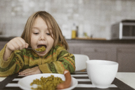 Portrait of little girl having lunch in the kitchen - KMKF00120