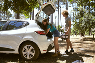 Young couple loading a car in forest - SRYF00699