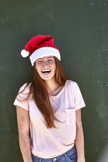 Portrait of laughing young woman wearing Christmas hat - SRYF00708