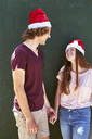 Young couple wearing Christmas hats smiling at each other - SRYF00711