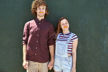 Young couple standing in front of a green wall with orange slices in their mouth - SRYF00714