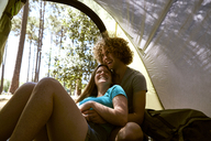 Happy young couple embracing in a tent - SRYF00717