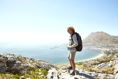 South Africa, Cape Town, smiling young man standing at the coast looking at view - SRYF00729