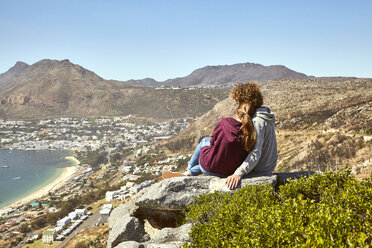 South Africa, Cape Town, young couple sitting at the coast looking at view - SRYF00732
