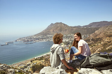 South Africa, Cape Town, smiling young couple sitting at the coast - SRYF00741
