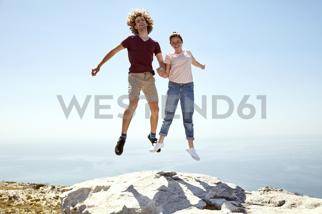 South Africa, Cape Town, happy young couple jumping on top of a mountain at the coast - SRYF00744
