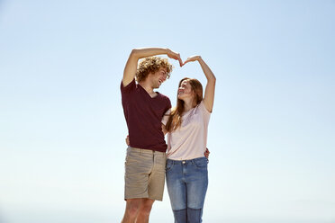 Happy young couple shaping a heart with their hands under blue sky - SRYF00747