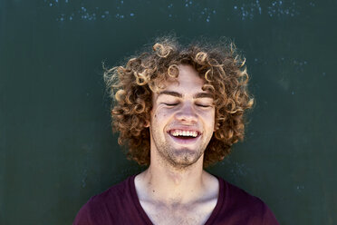 Portrait of laughing young man with curly hair in front of a green wall - SRYF00756