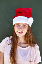 Portrait of smiling young woman wearing Christmas hat - SRYF00762