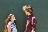 Smiling young couple in front of a green wall - SRYF00765
