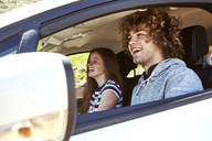Laughing young woman with boyfriend driving car - SRYF00768