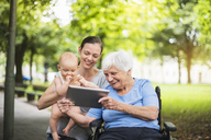 Grandmother, daughter and granddaughter having fun with tablet in a park - DIGF03210