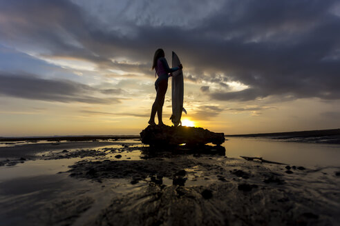 Indonesia, Bali, young woman with surfboard at sunset - KNTF00951