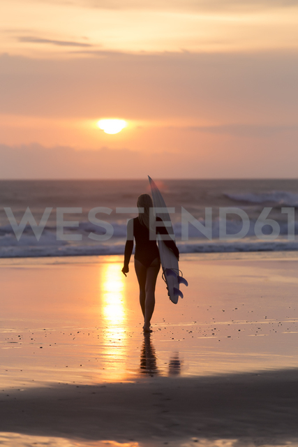 Indonesia, Bali, young woman with surfboard at sunset - KNTF00954