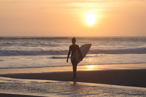 Indonesia, Bali, young woman with surfboard - KNTF00966