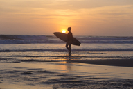 Indonesia, Bali, young woman with surfboard - KNTF00969