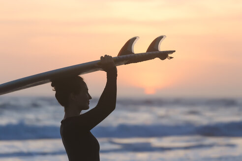 Indonesia, Bali, young woman with surfboard carrying on head at sunset - KNTF00972
