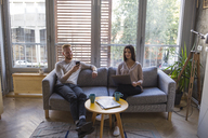 Couple sitting on couch with cell phone and laptop - MOMF00362
